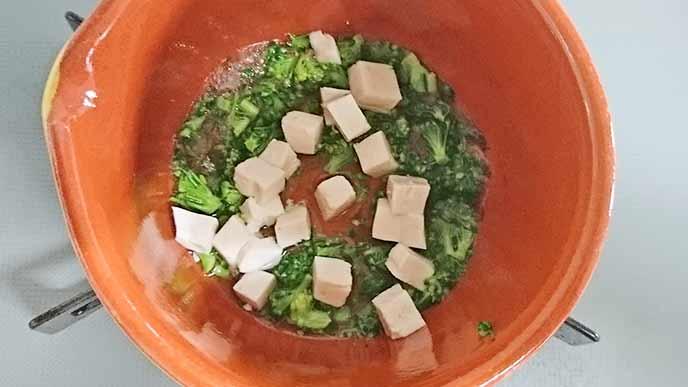 沸騰した鍋のお湯の中にある豆腐とブロッコリー