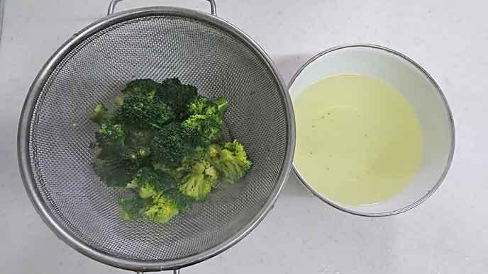 鍋ザルにあげられたブロッコリーとゆで汁