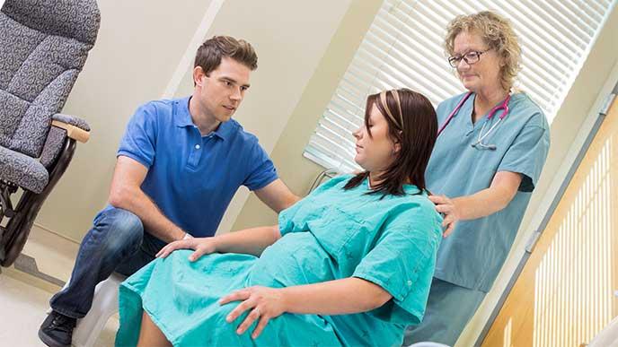 病院の椅子に座って分娩の準備をしてる妊婦さん