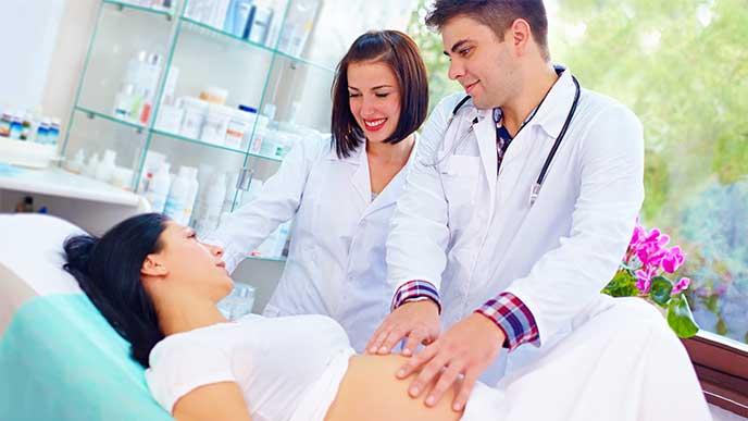 出産前に医師からお腹を診てもらってる妊婦さん