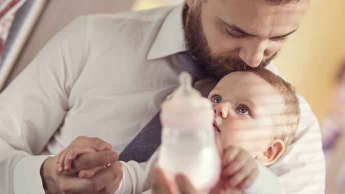 お父さんが哺乳瓶で赤ちゃんにミルクを飲ませる