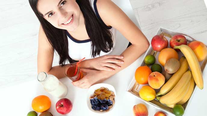 皿にドライフルーツを盛って食事に加える女性