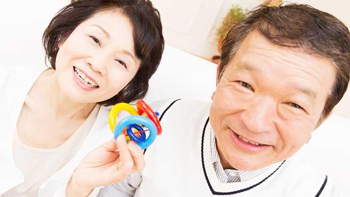 赤ちゃん用のおもちゃを手に笑顔の祖父母