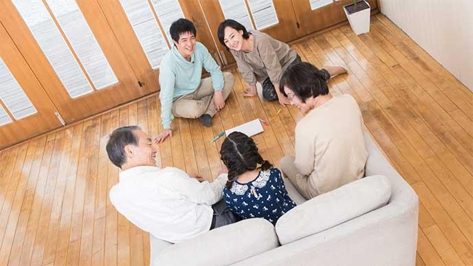 小学生の孫と話をする祖父母を笑顔で見てる両親