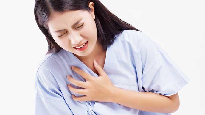 胸の痛みから手で押さえる女性