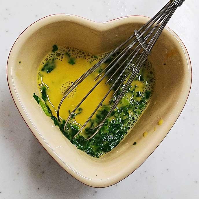 耐熱容器で小松菜と卵、だし汁を混ぜあわせる