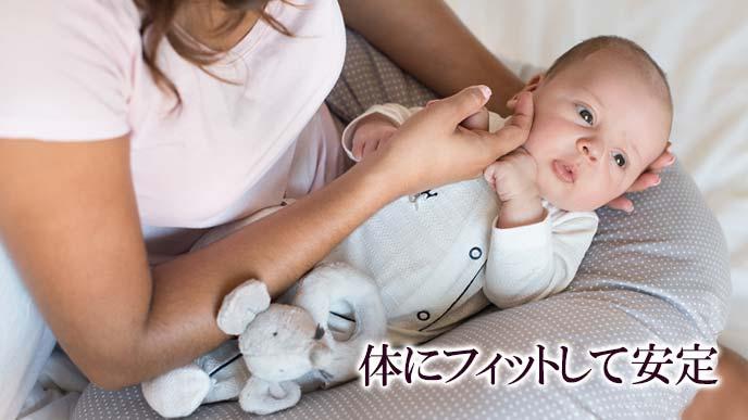 授乳クッションで赤ちゃんを固定する母親
