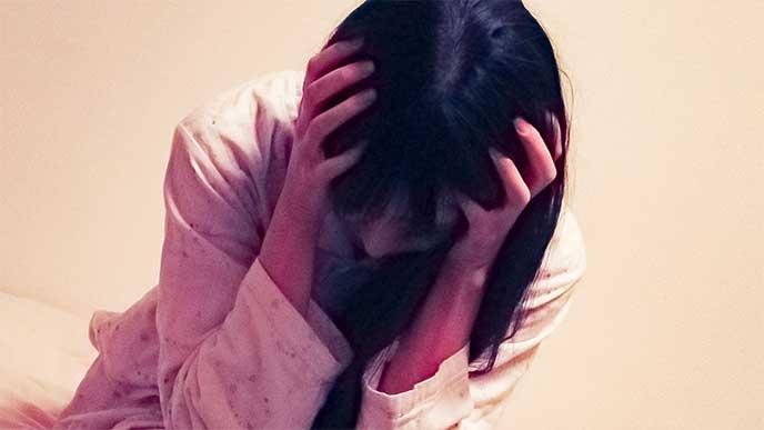 頭痛で頭を押さえる妊婦さん