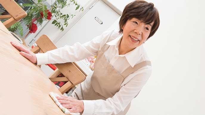 テーブルを拭いてる家事代行サービスの女性