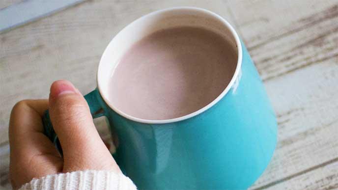 ココアが入ったカップを手にしてる女性