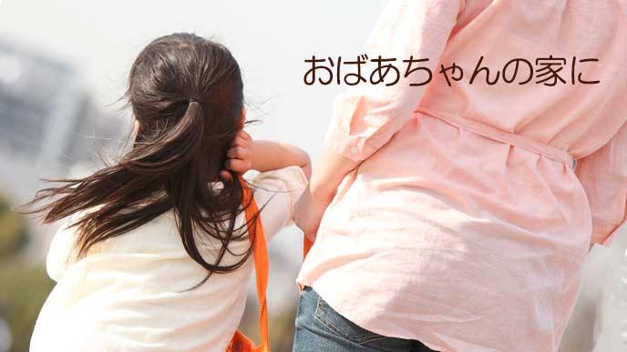 子供の手を引いて歩く母親