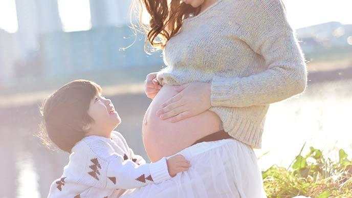 戸外で上の男の子と一緒に遊ぶ妊婦