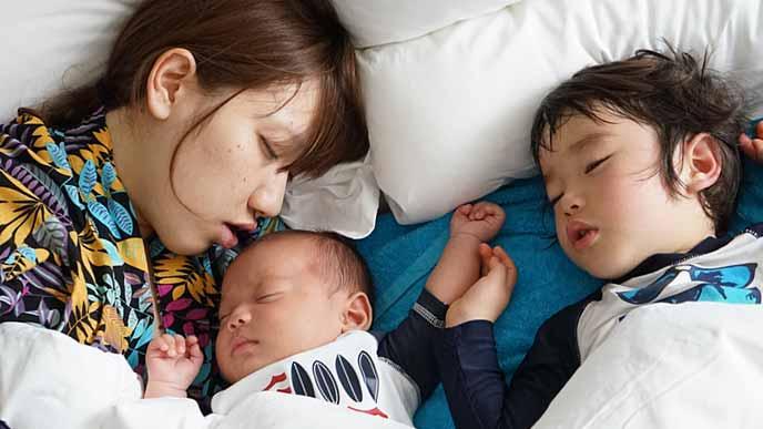 上の男の子と赤ちゃんと一緒に昼寝する女性