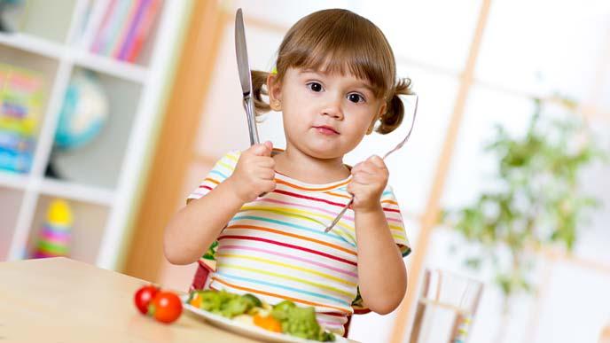 ナイフとフォークを持って食事に挑む幼児