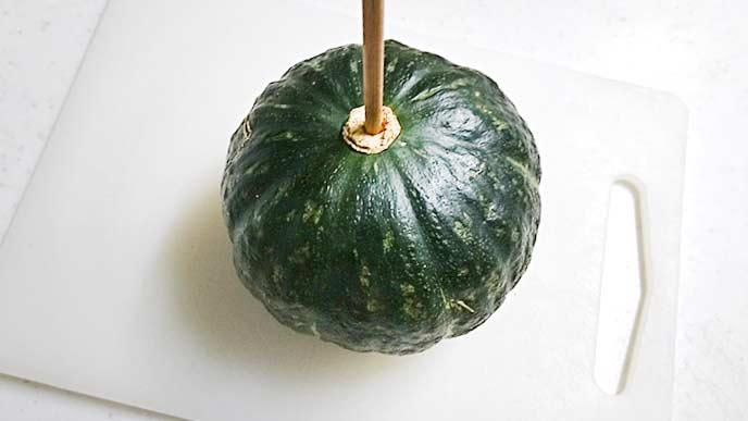 まな板の上でへたの部分に菜箸を刺されたかぼちゃ
