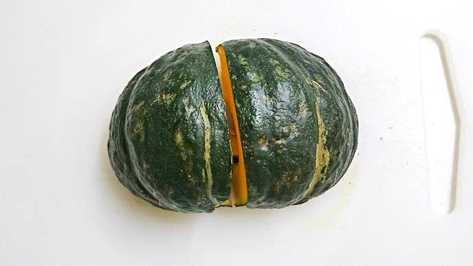 まな板の上で1/4カットにされるかぼちゃ