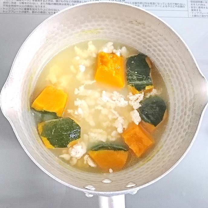 鍋の中でだし汁で茹でられたかぼちゃと鶏ひき肉
