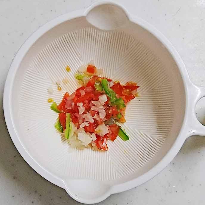 皿の中にあるみじん切りのミニトマトと玉ねぎとピーマン