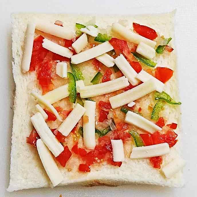 ピーマン、玉ねぎ、トマト、チーズがのった耳を切り落とした食パン