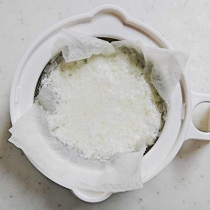 キッチンペーパーを敷いたザルで濾されるカッテージチーズ