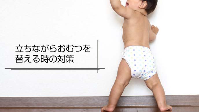 おむつをつけたままつかまり立ちをする赤ちゃん