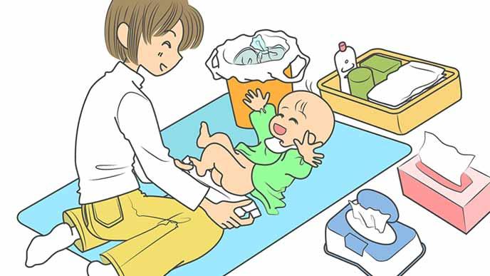 シートを敷き準備万端でオムツ替えをする母親