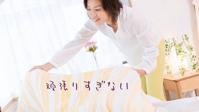 ベッドを片付ける母親