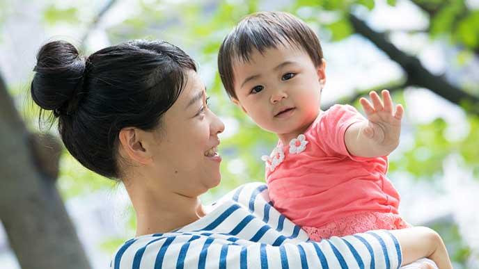 母親に抱っこされてバイバイと手を振る赤ちゃん