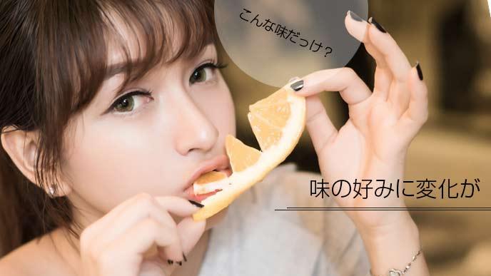 オレンジを食べている女性