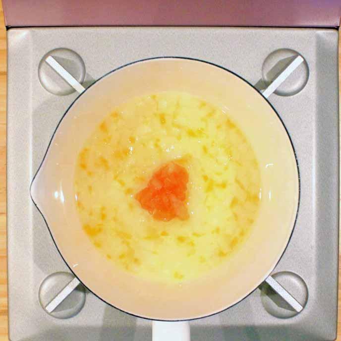 鍋で煮られるうどんとトマト