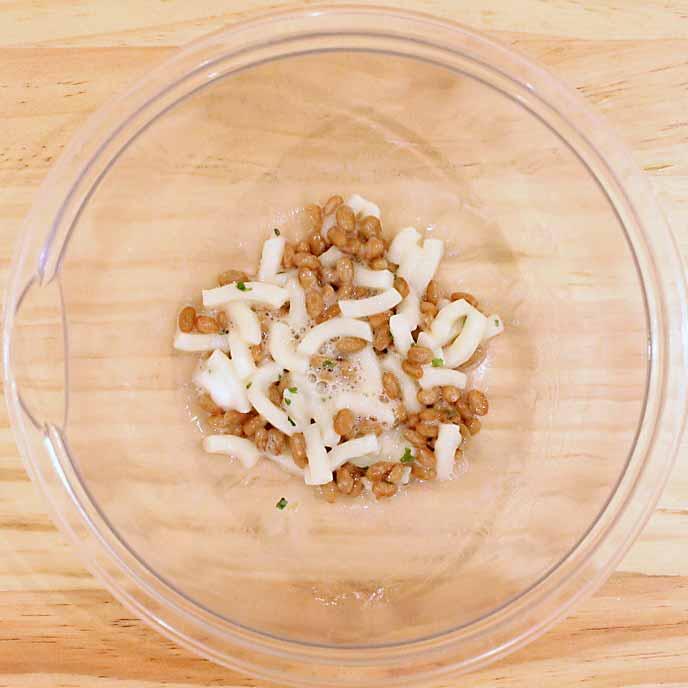 ボウルの中で混ぜられたうどんと納豆