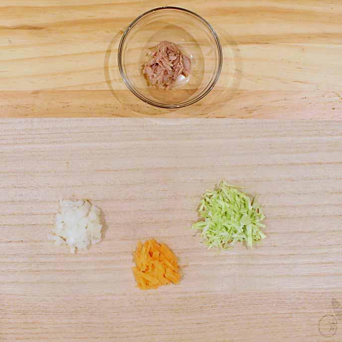 まな板のうえにある小さくカットされた野菜と、小皿に入ったツナの水煮