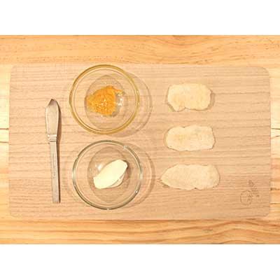 まな板のうえの赤ちゃんせんべいとお皿に入れたクリームチーズ、マーマレードジャム