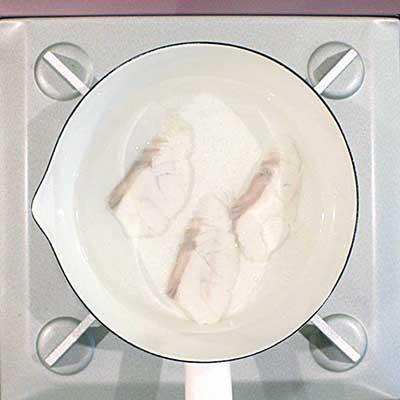 鍋で茹でられて白くなる真鯛