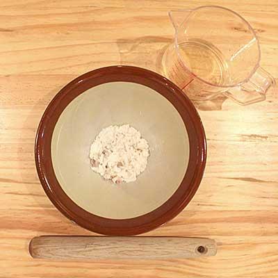 すり鉢の中でつぶされた真鯛とそばにある計量カップの中の昆布だし