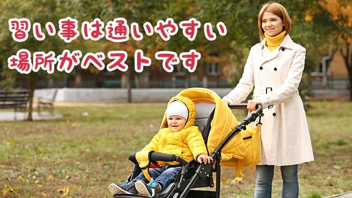 赤ちゃんをベビーカーに乗せ公園を散歩している母親