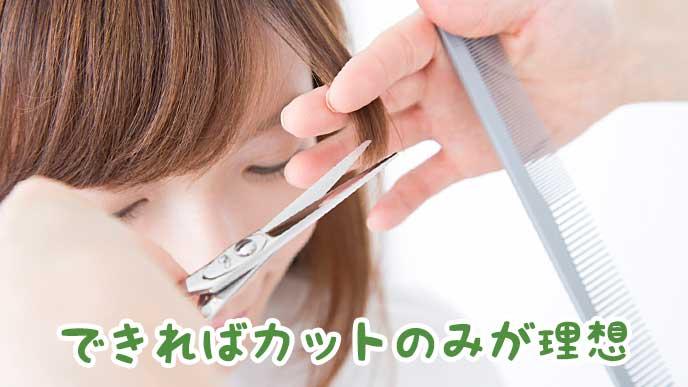 美容師にヘアカットしてもらっている女性