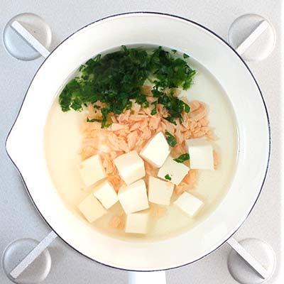 だし汁の入った鍋に入れられる鮭・小松菜・豆腐