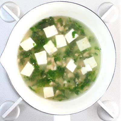 鍋で煮こまれる鮭・小松菜・豆腐