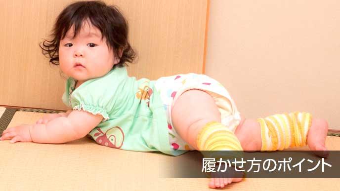 部屋の中でレッグウォーマーをつけてハイハイする赤ちゃん
