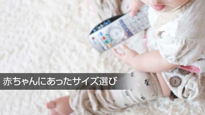 テレビのリモコンをもって遊ぶレッグウォーマーをつけた赤ちゃん