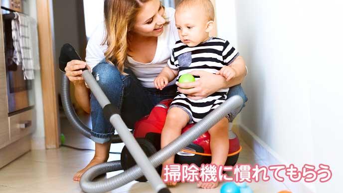 赤ちゃんを抱っこしながら掃除機をかけているお母さん