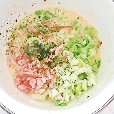 ボウルの中で混ぜ合わせられる肉やキャベツ、小麦粉や卵、水