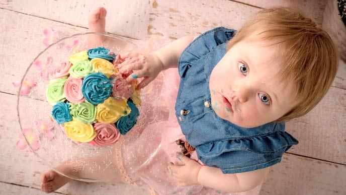 ケーキを食べながら上を見上げる赤ちゃん