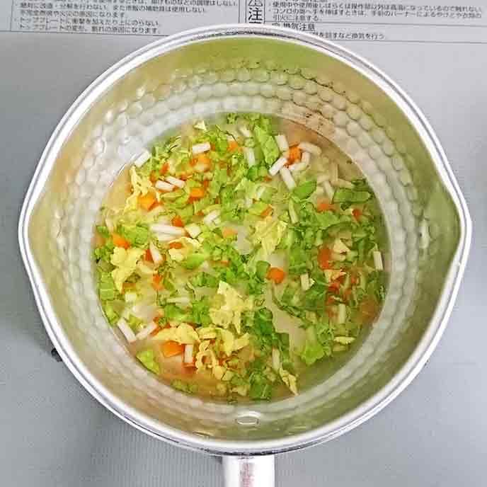 だし汁の中で煮られるもやしと人参と白菜