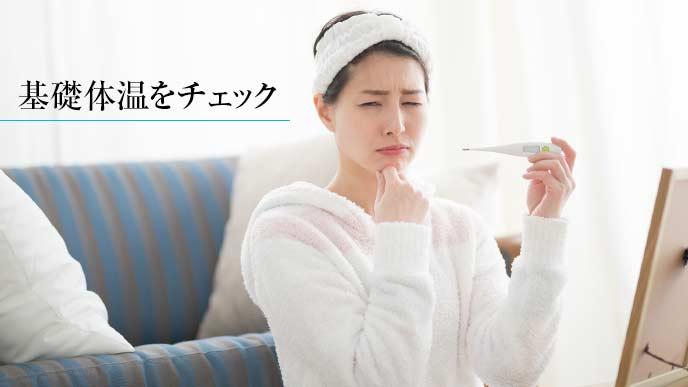 基礎体温を測っている寝起きの女性