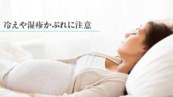 布団の上で横になっている妊婦