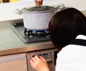 鍋を火にかける主婦