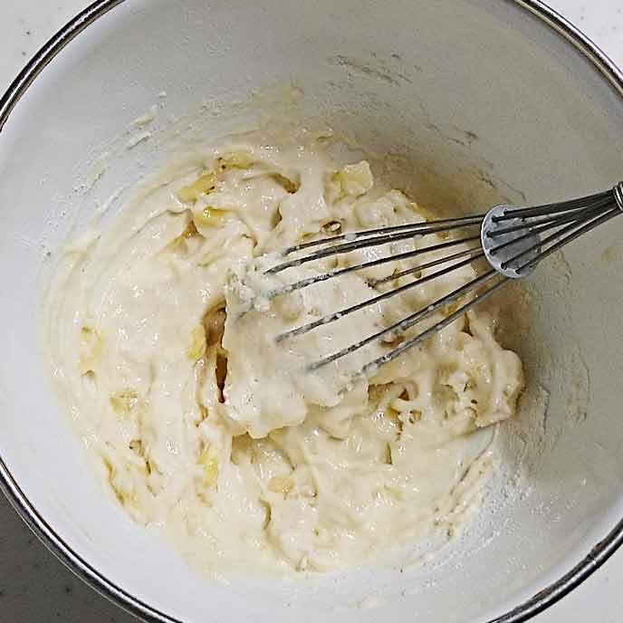 ボウルの中で混ぜられる小麦粉とバナナ