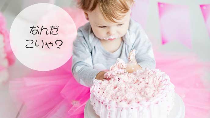 初めてのケーキを舐める女の子の赤ちゃん